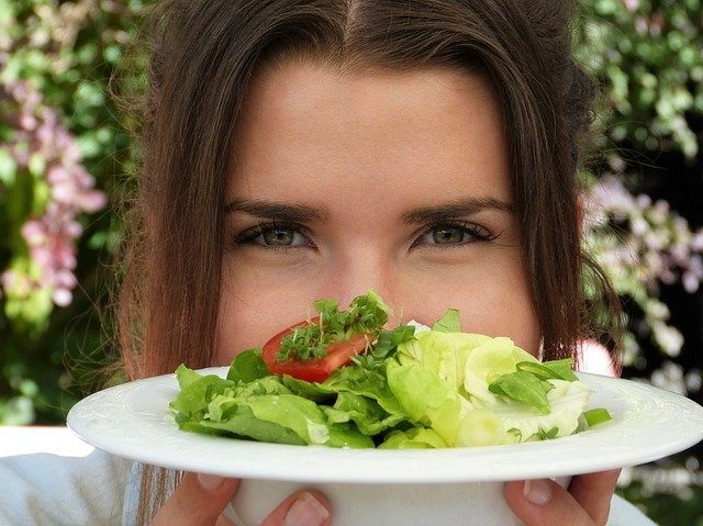 A person sitting at a table with a plate of food with broccoli